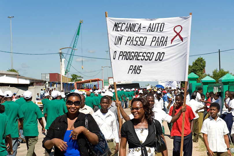 1st of May rally workers carry a banner with <p>HIV/AIDS ribbon to create awareness