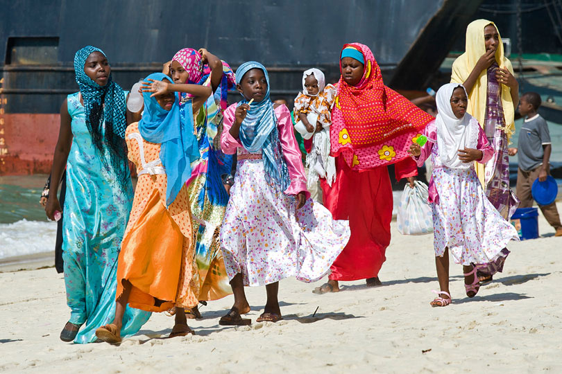 Women wearing traditional dresses <p>on the beach in Stone Town